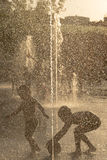 Silhouette of a kid playing in a sunny water fountain Stock Photo