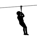 Silhouette of a kid playing with a tyrolean traverse Stock Photos