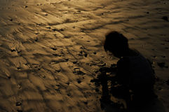 Silhouette Kid. A kid plays sand on the Kuta Beach, Bali while the sunset is coming up Royalty Free Stock Image