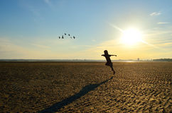 Silhouette of kid running on beach Stock Images