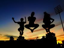 Silhouette of 3 kids jumping Stock Image