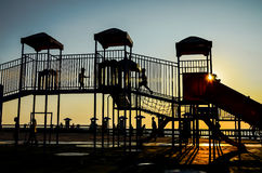 Silhouette of Kids playing at playground with sunset sky Royalty Free Stock Photos