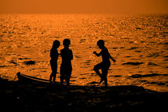 Silhouette of Kids playing and walking on beach Stock Photos