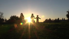 Silhouette of kids running away at sunset. Silhouette of happy kids running away together at sunset, slow motion stock video footage