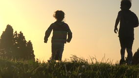 Silhouette of kids running away at sunset. Silhouette of happy kids running away together at sunset, slow motion, camera following from behind stock video footage