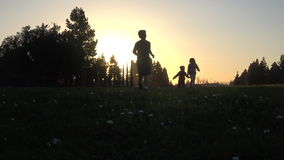 Silhouette of kids running at sunset stock video footage