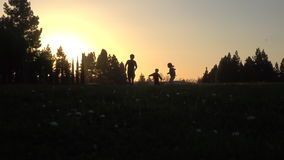 Silhouette of kids running at sunset stock video
