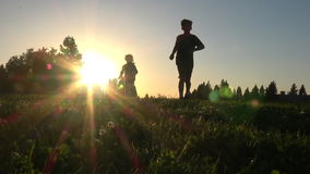 Silhouette of kids running at sunset. Silhouette of happy kids running together at sunset, slow motion stock video