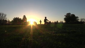 Silhouette of kids running at sunset stock footage