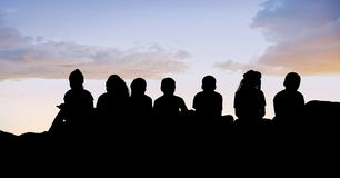 Silhouette kids sitting on hill against sky Stock Image
