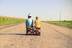 Silhouette of kids sitting on the suitcase over. Back view of children on the suitcase over countryside rural road on sunny blue sky outdoors background Stock Image
