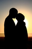 Silhouette Kiss. Couple kissing at sunset or sunrise Royalty Free Stock Photography