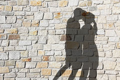 Silhouette of kissing couple, against natural stone wall.  Royalty Free Stock Photography