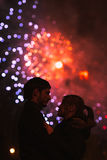 A silhouette of a kissing couple in front of a huge fireworks display. royalty free stock photo