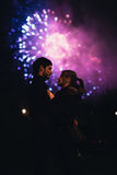A silhouette of a kissing couple in front of a huge fireworks display. stock photography