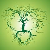 Silhouette of kissing couple shaped by tree. Stock Image