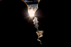 Silhouette of kissing couple in winter park. On sun background Stock Photo