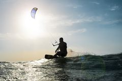 Kite surfer sailing in front of the sunset Stock Photography