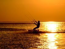 Silhouette of a kitesurf 2. Silhouette of a kitesurf on a gulf on a sunset 2 Stock Photos