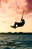 Silhouette of a kitesurfer flying Stock Image