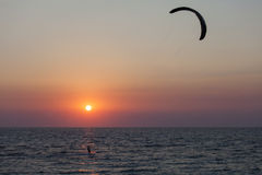 Silhouette of a kitesurfer sailing at sunset Royalty Free Stock Image