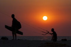 Silhouette of a kitesurfer sailing at sunset Stock Image