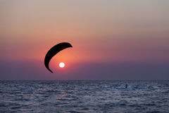 Silhouette of a kitesurfer sailing at sunset Stock Photography