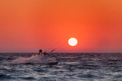 Silhouette of a kitesurfer sailing at sunset Stock Images