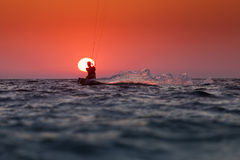 Silhouette of a kitesurfer sailing at sunset over the sun Stock Photos