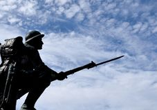 Silhouette of a kneeling WWI soldier statue. Silhouette of a kneeling Canadian WWI soldier statue with a backpack and gun with bayonet, blue sky with white stock image