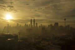 Silhouette of Kuala Lumpur City during dramatic sunrise on hazy day Stock Image