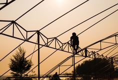 Silhouette labor on the roof in the sunset Stock Image