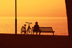 Silhouette of lady and bike looking out to sea Stock Photography