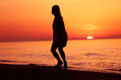 Silhouette of a lady dancing on the beach Stock Photos
