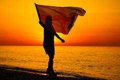Silhouette of a lady dancing with a flag Royalty Free Stock Photography