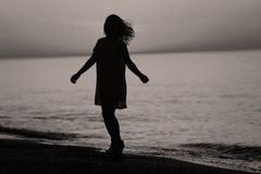 Silhouette of a lady dancing. Silhouette of a girl dancing on the beach at sunrise Stock Photography