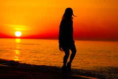 Silhouette of a lady dancing by the sea Royalty Free Stock Images