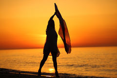 Silhouette of a lady dancing by the sea Stock Image