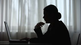 Silhouette of lady feeling rush of heat and dizziness working on laptop at night stock footage