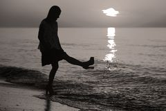 Silhouette of a lady jumping by the sea Royalty Free Stock Photography