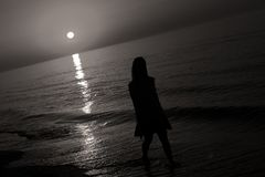 Silhouette of a lady jumping by the sea Royalty Free Stock Image