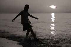Silhouette of a lady jumping by the sea Stock Photos
