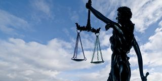 Silhouette of lady justice against a dramatic sky. stock image