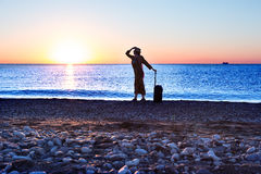 Silhouette of Lady staying on Sea Surf holding Travel Suitcase Royalty Free Stock Photography