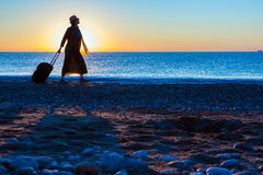 Silhouette of Lady walking along Sea Surf pulling Travel Suitcase Royalty Free Stock Photography