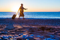 Silhouette of Lady walking along Sea Surf pulling Travel Suitcase Royalty Free Stock Photos