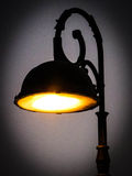 A silhouette of a lamppost. A antique isolated lamppost lit in the dark Stock Images