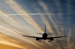 Silhouette of landing airplane at dawn Royalty Free Stock Photography