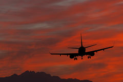 Silhouette of landing airplane at dawn Stock Image