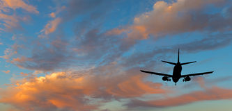 Silhouette of landing airplane at dawn. Composite image symbolizing traveling by modern aircraft Royalty Free Stock Photos
